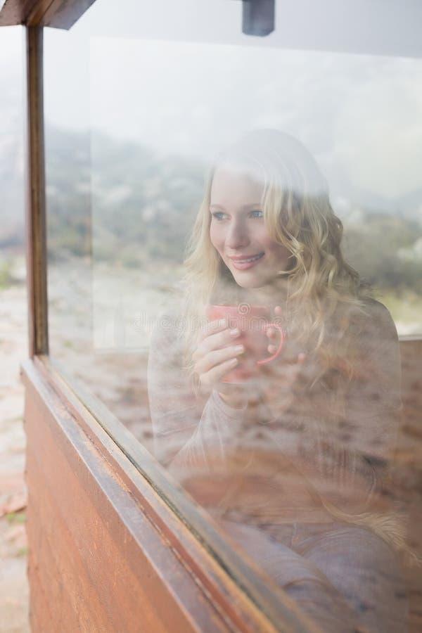 Donna contenta premurosa con la tazza di caffè che guarda attraverso la finestra fotografia stock libera da diritti