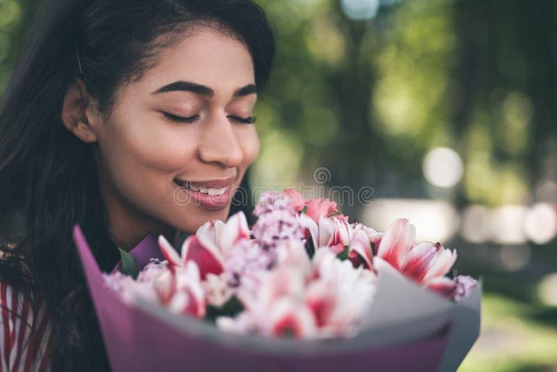 Donna contentissima che odora i fiori e sorridere immagini stock libere da diritti