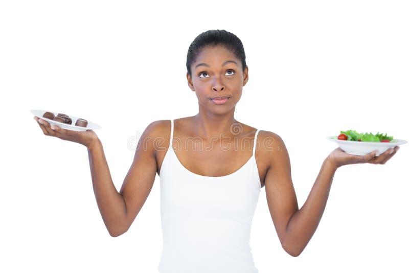 Donna contrastante che decide di mangiare sano oppure no fotografie stock libere da diritti