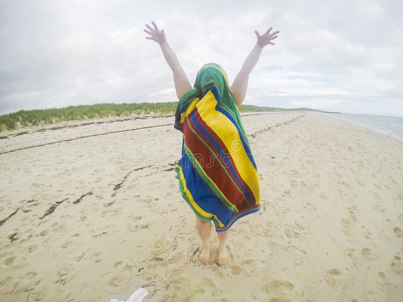 Donna coperta di asciugamano a strisce alla spiaggia in Truro, mA fotografie stock libere da diritti
