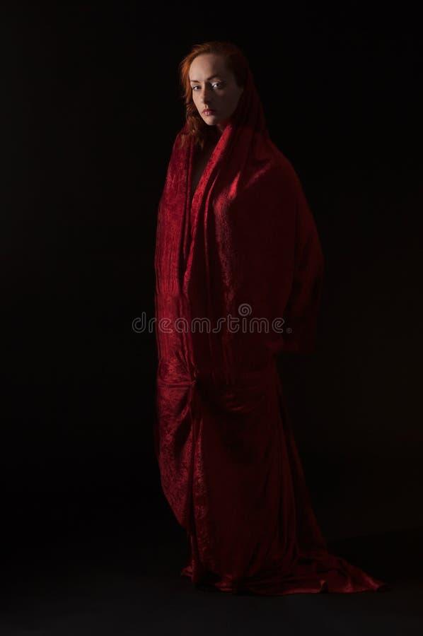 Donna coperta nel tessuto rosso del velluto fotografia stock libera da diritti