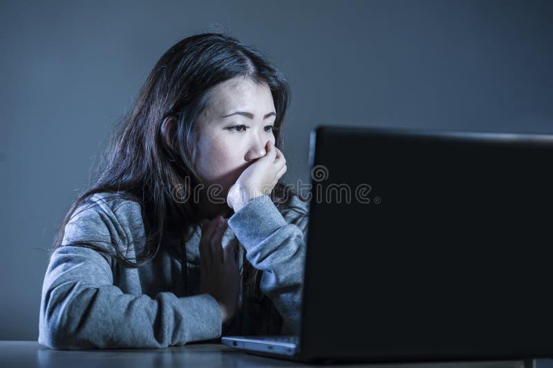 Donna coreana asiatica abbastanza triste dello studente che sembra studio diminuito e preoccupato con il computer portatile nello fotografie stock libere da diritti