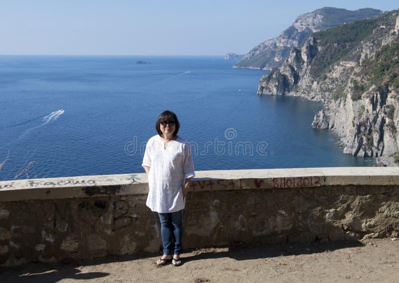 Donna coreana che gode del paesaggio lungo la costa di Amalfi, Italia di vacanza fotografia stock