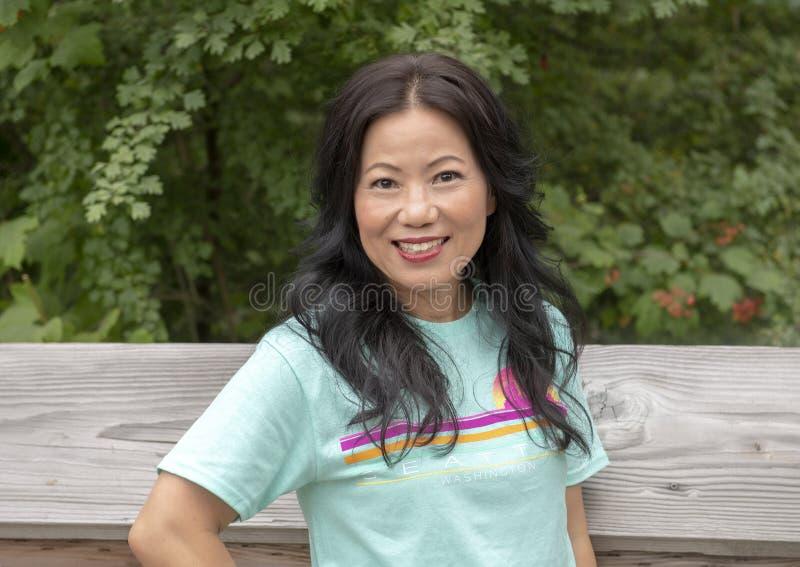 Donna coreana di cinquantatre anni che posa su un ponte di legno in Washington Park Arboretum, Seattle, Washington immagine stock libera da diritti