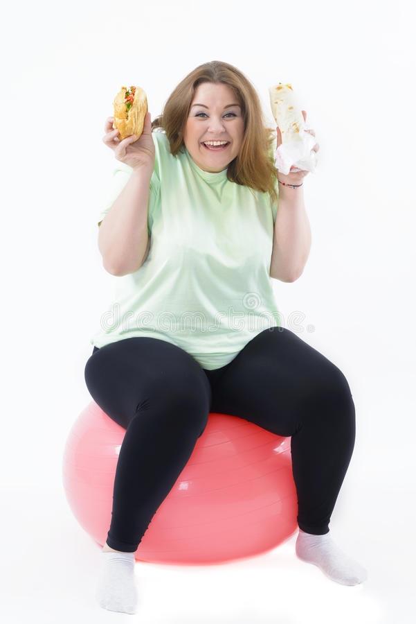 Donna corpulenta che ha dipendenza ad alimento non sano fotografie stock