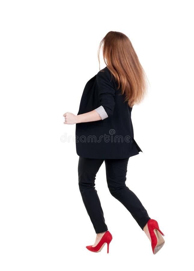 Donna corrente di affari Vista posteriore ragazza andante in vestito Ri immagine stock