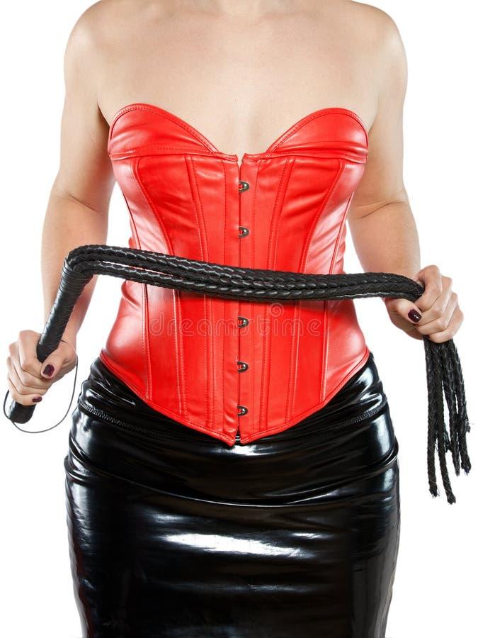 Donna in corsetto di cuoio rosso con la frusta nera immagine stock