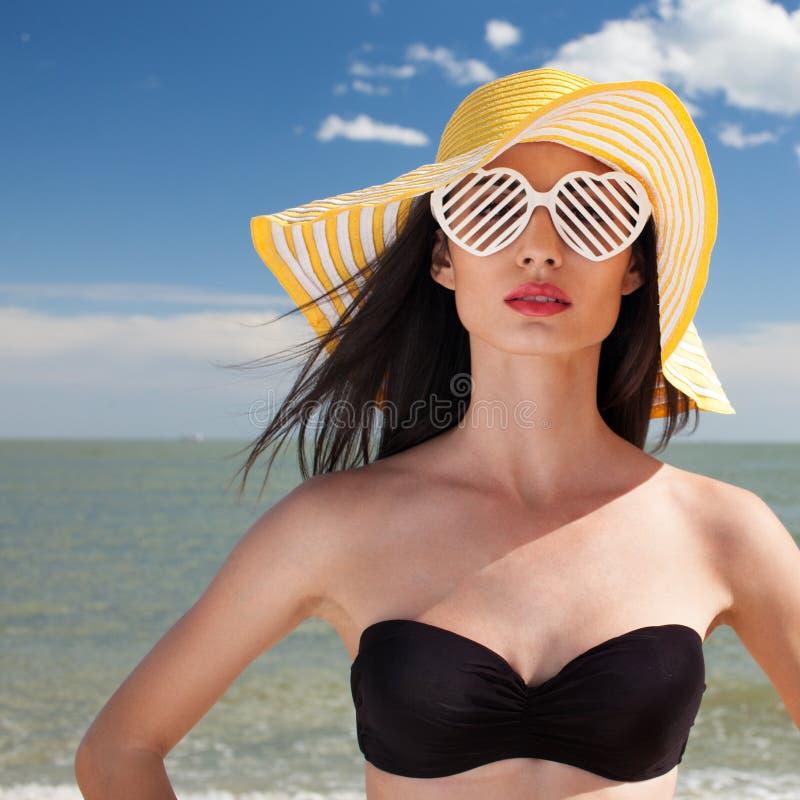 Donna in costume da bagno alla moda sulla spiaggia fotografia stock