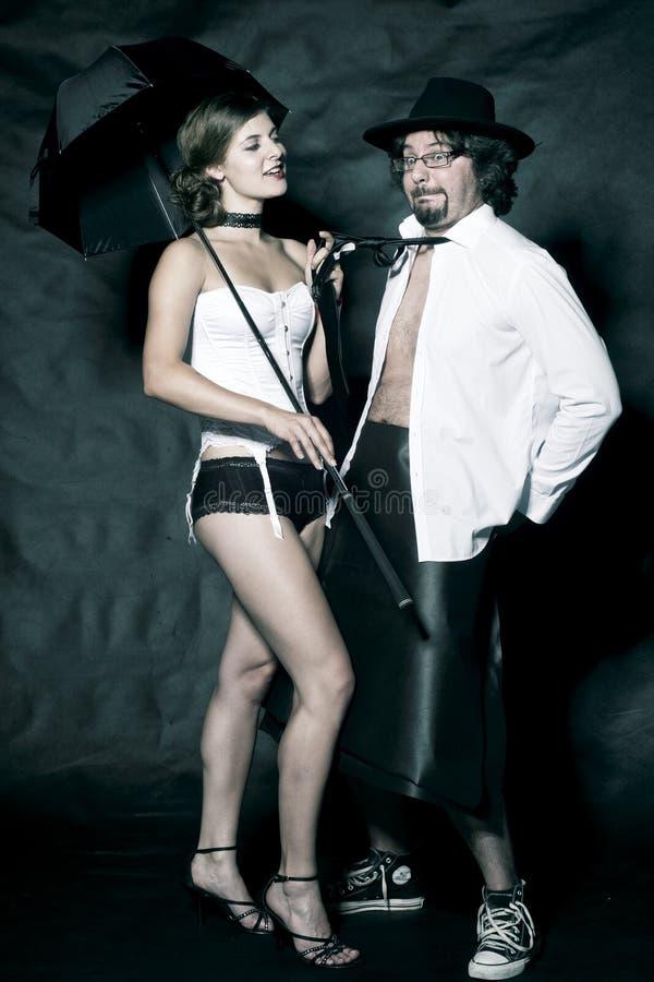 Donna in costume ed in uomo sexy in camicia bianca con lo smoking ed il cappello immagini stock