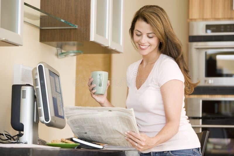 Donna in cucina al calcolatore con caffè immagini stock