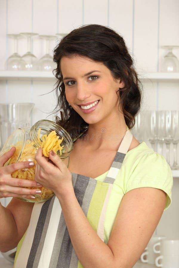 Donna in cucina con pasta fotografia stock libera da diritti