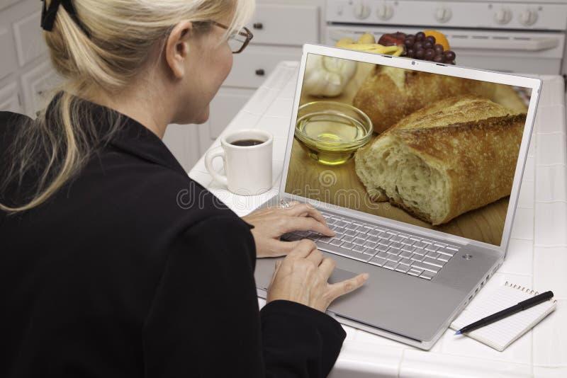 Donna In Cucina Per Mezzo Del Computer Portatile - Alimento E Ricette Fotografia Stock Libera da Diritti