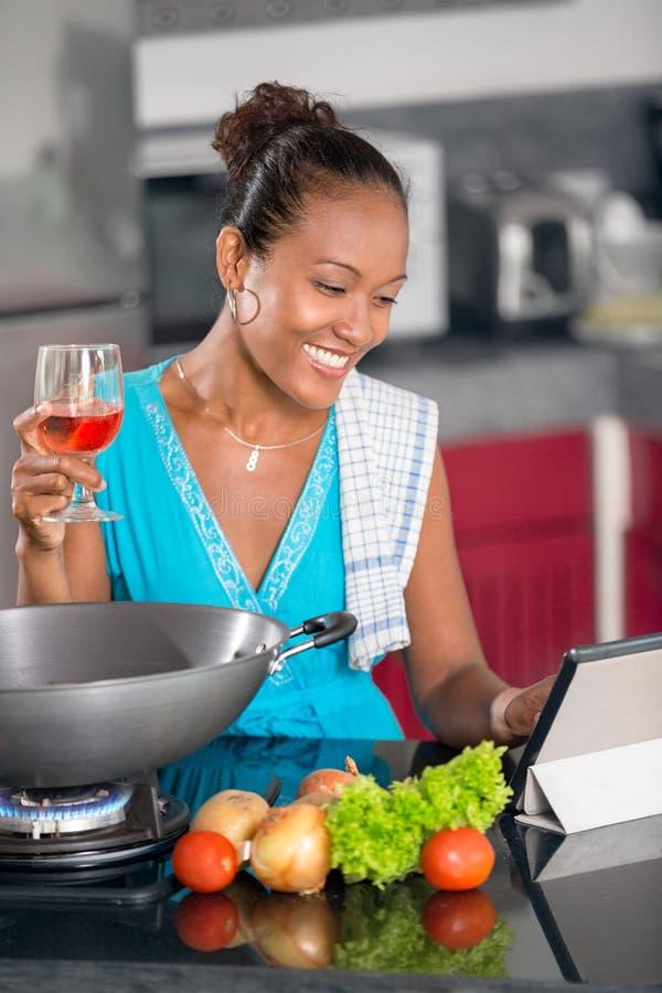 Donna in cucina a seguito della ricetta sulla compressa di Digital fotografia stock libera da diritti