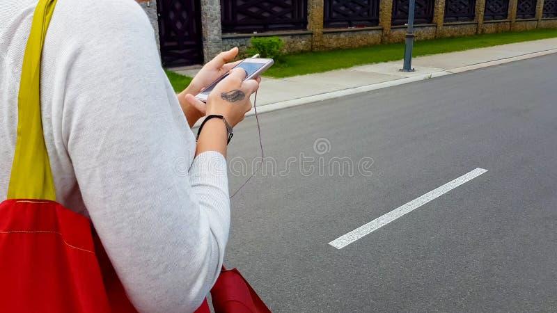 Donna in cuffie che cammina sulla via della città, guardante in smartphone, applicazione immagini stock libere da diritti