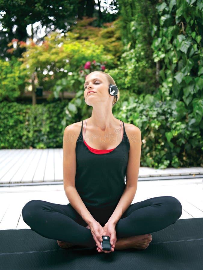 Donna in cuffie che fanno yoga rt immagini stock