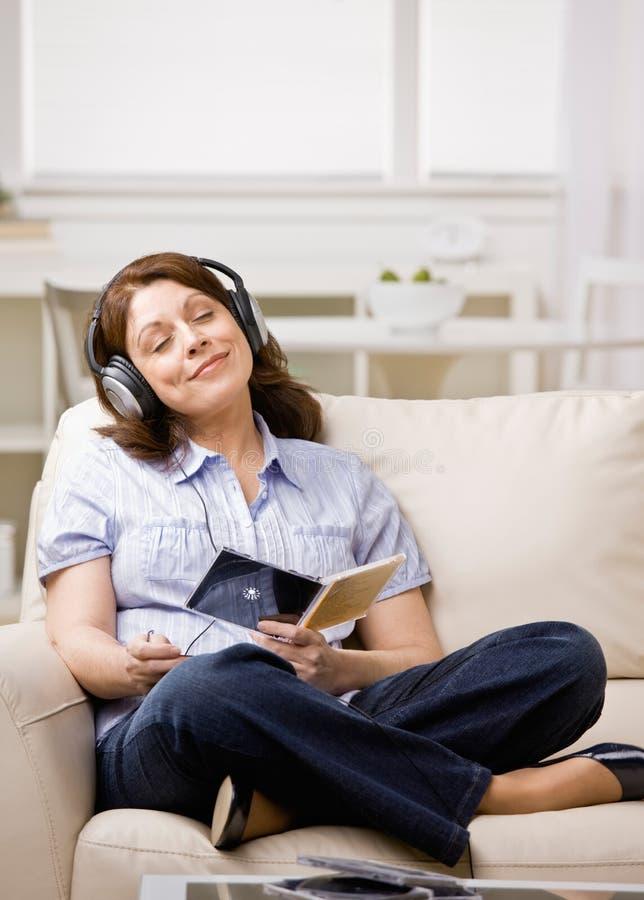 Donna in cuffie chegode dell'ascoltare il Cd di musica fotografia stock