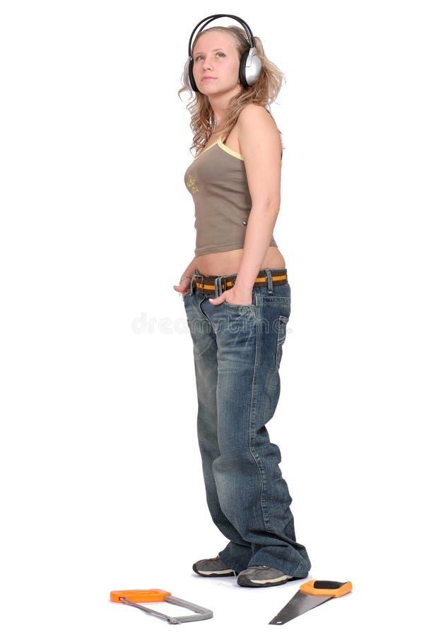 Donna in cuffie con una sega immagine stock