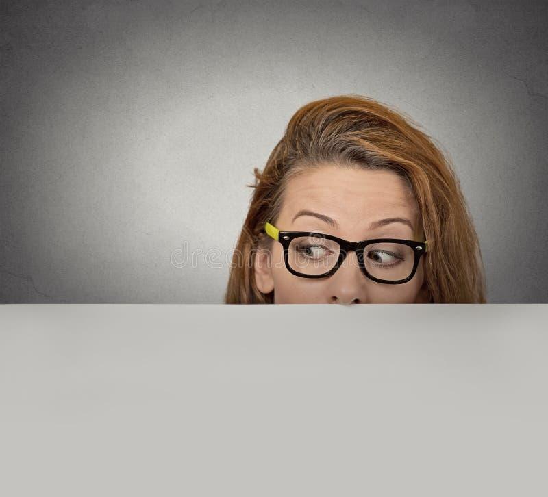 Donna curiosa che dà una occhiata sopra il bordo del tabellone per le affissioni di carta vuoto in bianco fotografia stock libera da diritti