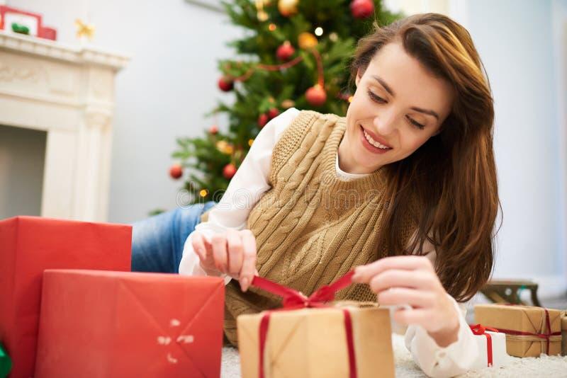 Donna curiosa che non imballato il contenitore di regalo di Natale fotografia stock libera da diritti