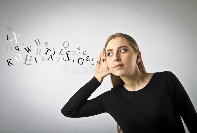 Donna curiosa nel nero e nelle lettere fotografie stock