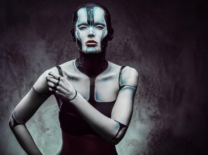 Donna cyber sensuale con trucco creativo Concetto di futuro e di tecnologia Isolato su un fondo strutturato scuro immagini stock