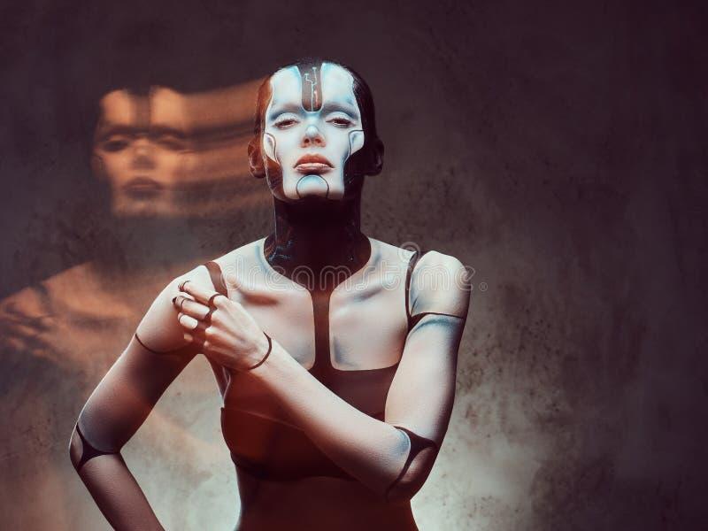 Donna cyber sensuale con trucco creativo Concetto di futuro e di tecnologia Isolato su un fondo strutturato scuro fotografia stock