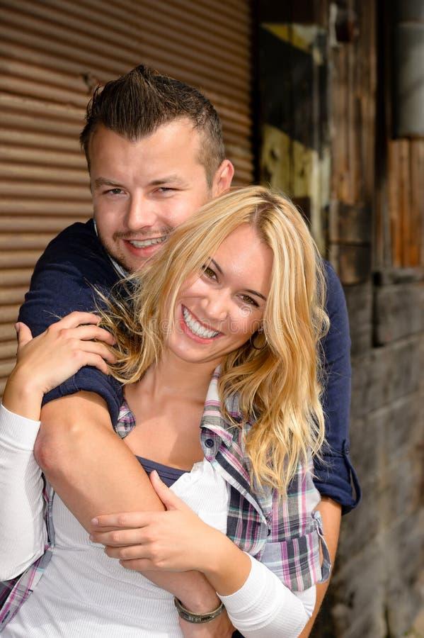 Donna d'abbraccio dell'uomo e rilassamento sorridente eccitati fotografie stock