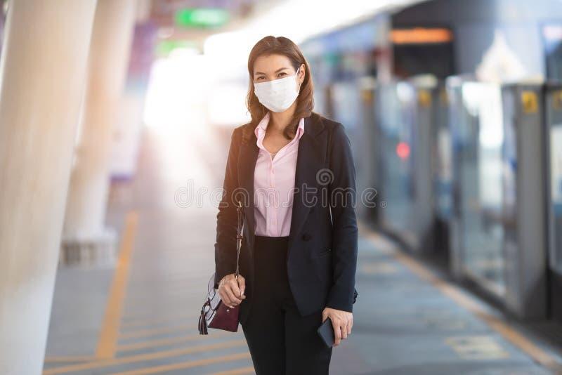 Donna d'affari che indossa una maschera in attesa del treno fotografia stock libera da diritti