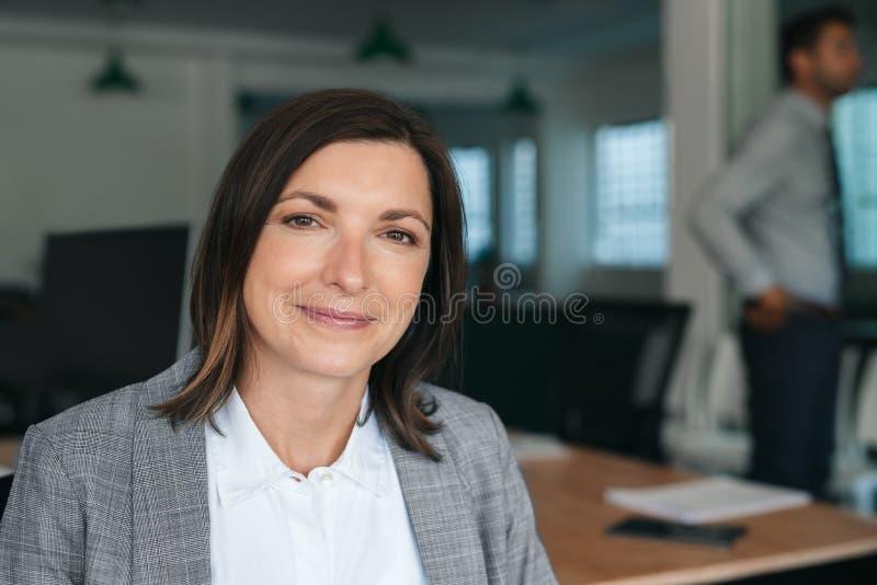 Donna d'affari sorridente seduta al lavoro con i colleghi sullo sfondo fotografie stock