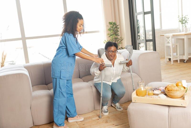 Donna d'aiuto dell'infermiere da stare dal sofà con le grucce immagini stock