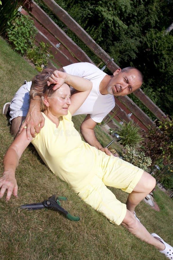 Donna d'aiuto dell'uomo con il colpo di calore immagini stock libere da diritti