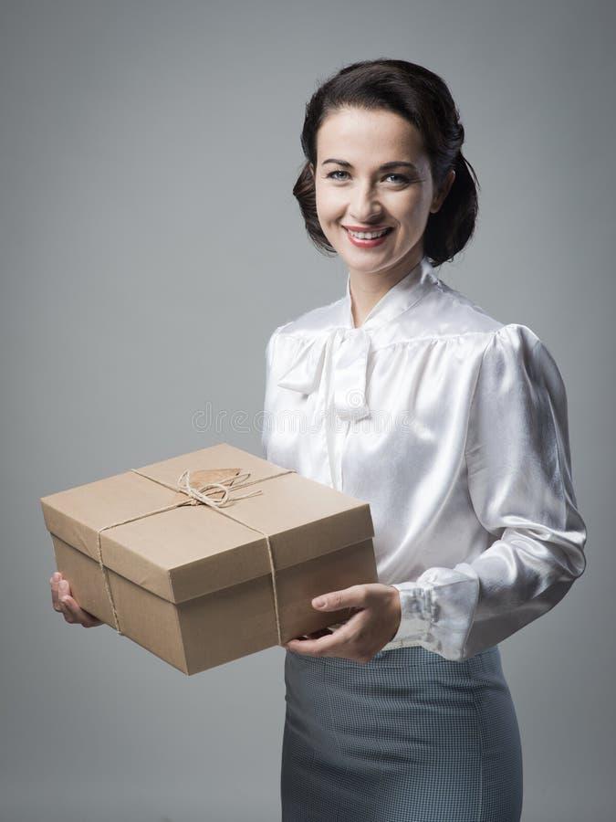 Donna d'annata sorridente con il pacchetto della posta fotografia stock libera da diritti