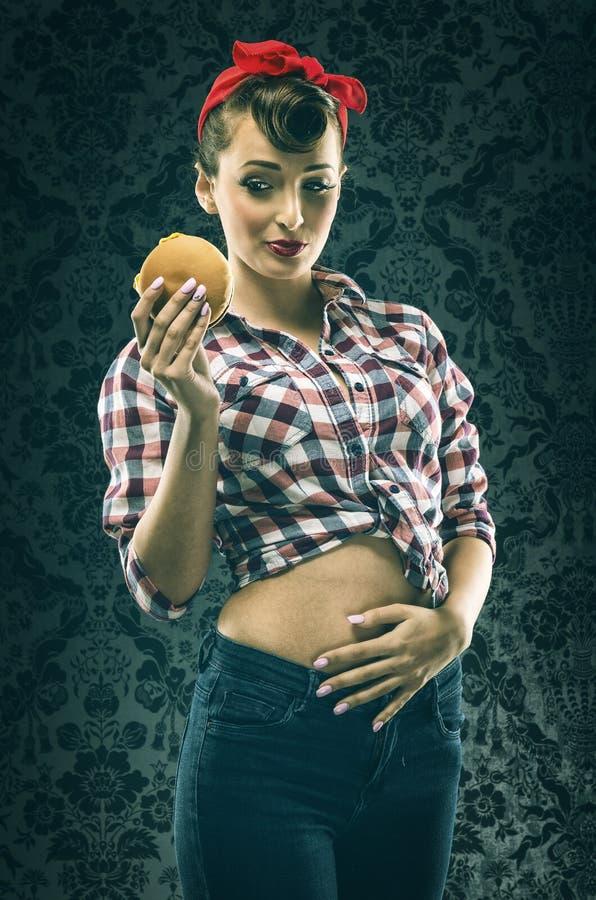 Donna d'annata in vestito antiquato, mangiante gli hamburger immagini stock