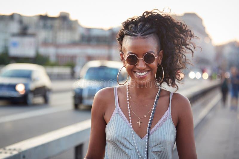 Donna d'avanguardia in camisole ed occhiali da sole a strisce, ritratto immagine stock