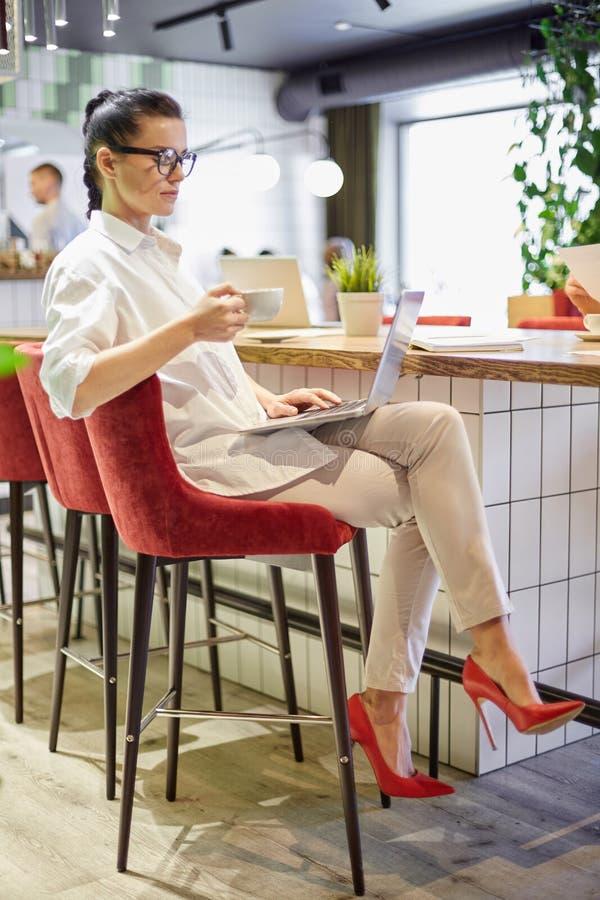 Donna d'avanguardia con caffè ed il computer portatile fotografia stock