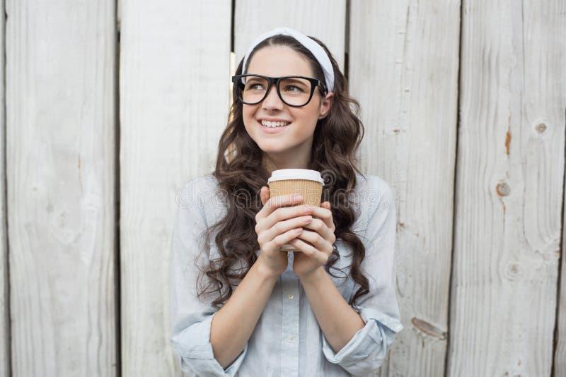 Donna d'avanguardia pensierosa con i vetri alla moda che tengono caffè immagini stock