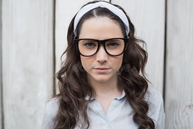 Donna d'avanguardia seria con la posa alla moda di vetro fotografia stock