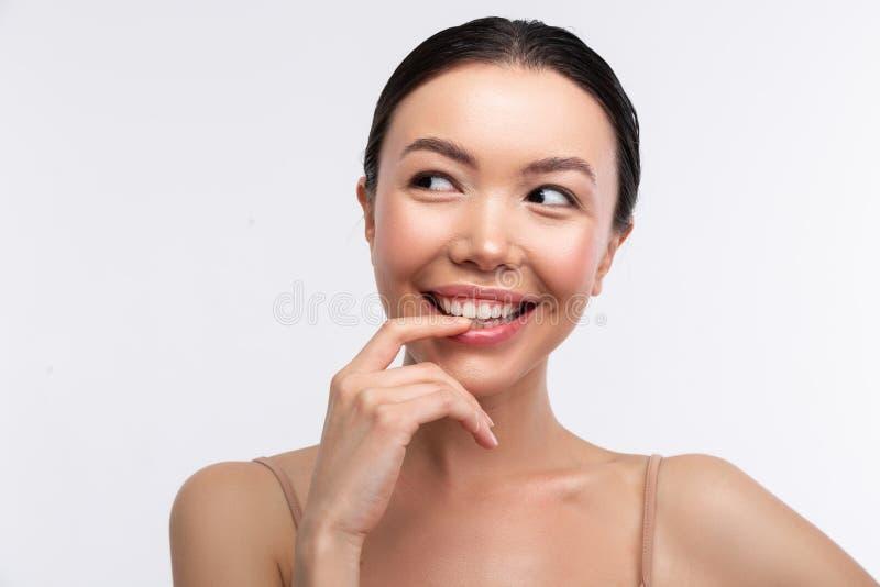Donna d'orientamento dagli occhi scuri che ritiene premurosa ed emozionante fotografia stock