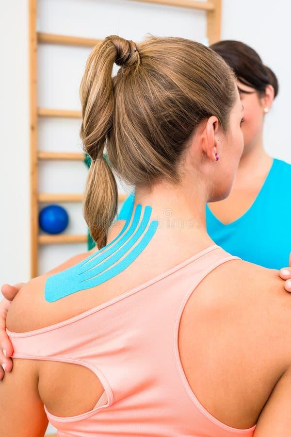 Donna da dietro con nastro adesivo di Kinesio sulla spalla in fisioterapia fotografie stock
