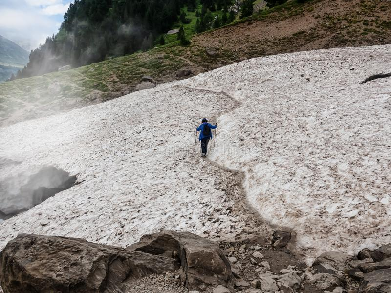 Donna da solo coraggiosa con i bastoni per l'escursione degli incroci un ghiacciaio nelle montagne fotografia stock libera da diritti