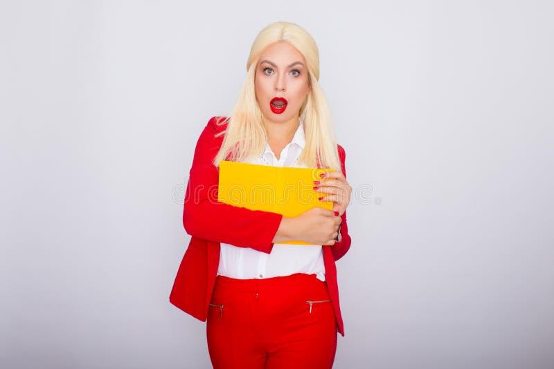 Donna dai capelli bionda attraente che porta rivestimento rosso ed i pantaloni, tenenti libro in sue mani fotografia stock libera da diritti