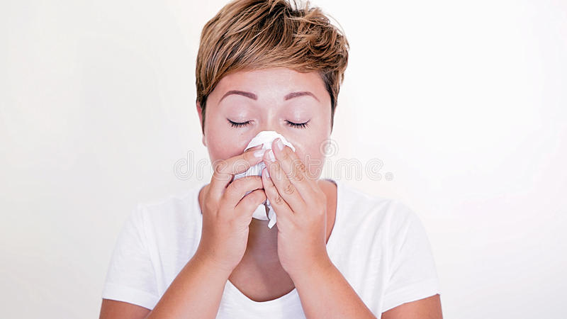 Donna dai capelli corti che soffia il suo naso sui precedenti bianchi immagine stock