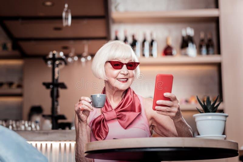 Donna dai capelli corti sorridente con rossetto luminoso che porta la tazza di caffè minuscola immagini stock