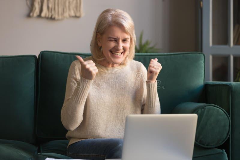 Donna dai capelli grigia emozionante felice che celebra vittoria online, facendo uso del computer portatile immagini stock libere da diritti