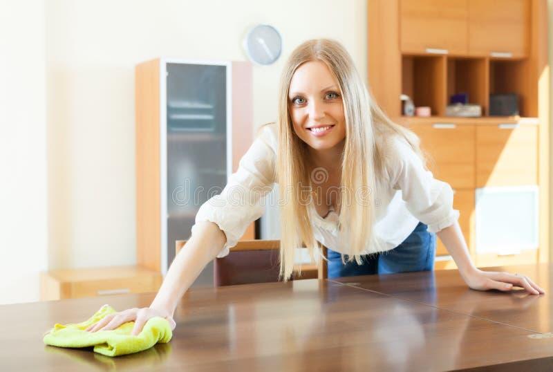 Donna dai capelli lunghi bionda allegra che pulisce la polvere fotografia stock libera da diritti