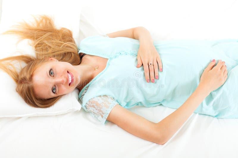 Donna dai capelli lunghi bionda di gravidanza che si trova sullo strato bianco sulla sua b fotografia stock libera da diritti