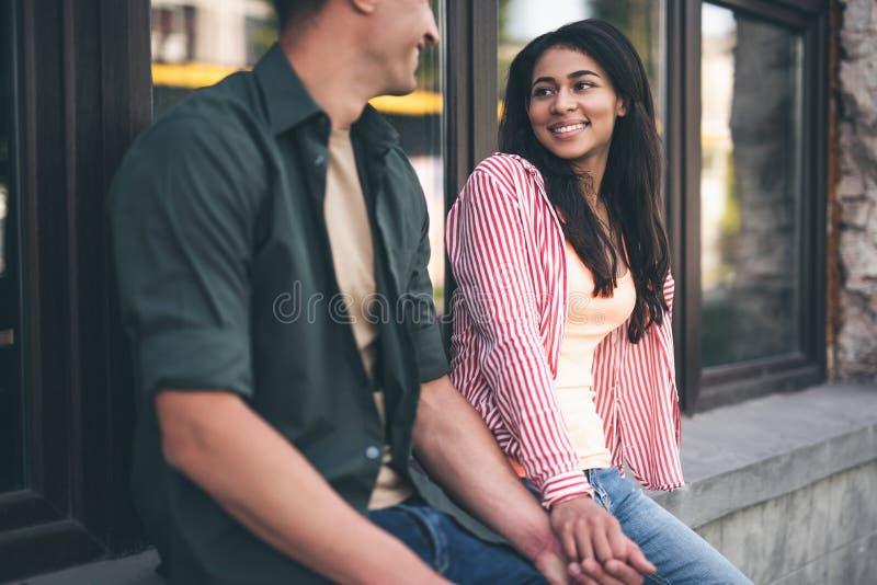 Donna dai capelli lunghi che esamina uomo caro e sorridere fotografie stock