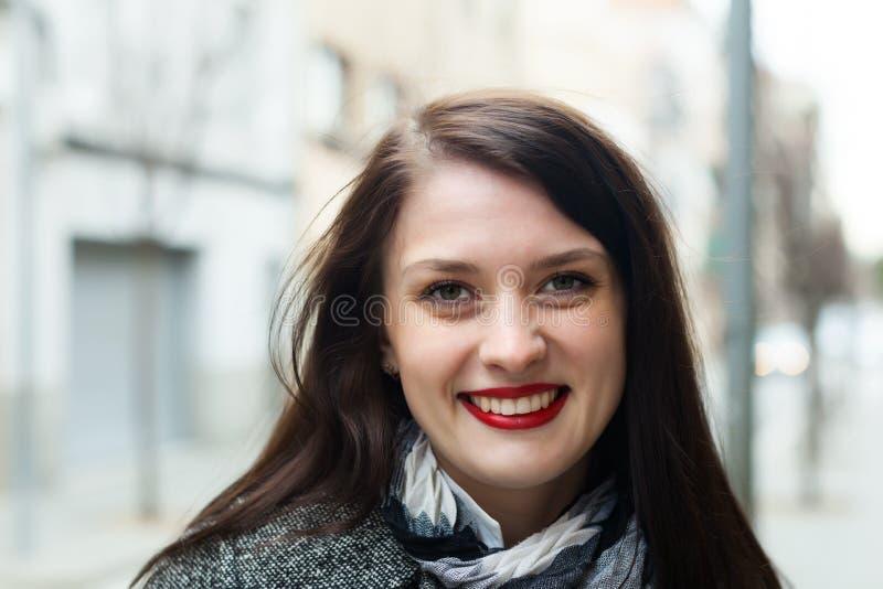 Donna dai capelli lunghi felice in via di autunno fotografia stock