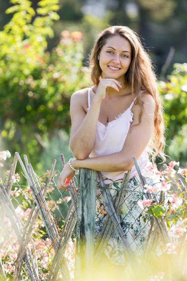 Donna dai capelli lunghi felice vicino al recinto fotografia stock libera da diritti