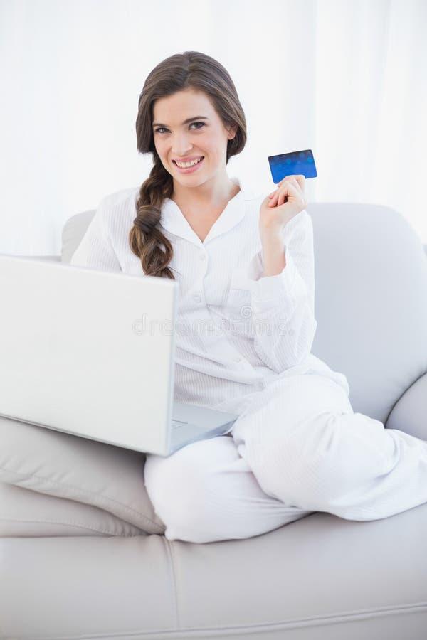 Donna dai capelli marrone abbastanza casuale in pigiami bianchi che compera online con il suo computer portatile fotografia stock libera da diritti